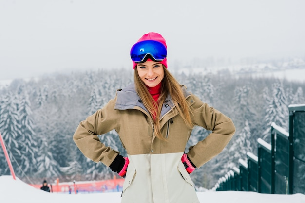 Giovane donna sorridente sportiva in inverno con lo snowboard, occhiali