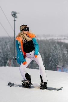 Giovane donna sorridente sportiva in inverno con lo snowboard