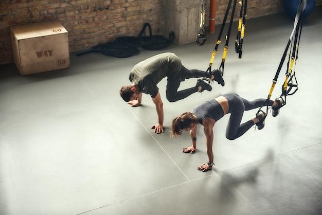 Vista dall'alto giovane e sportiva di una coppia in allenamento sportivo con cinturini fitness trx