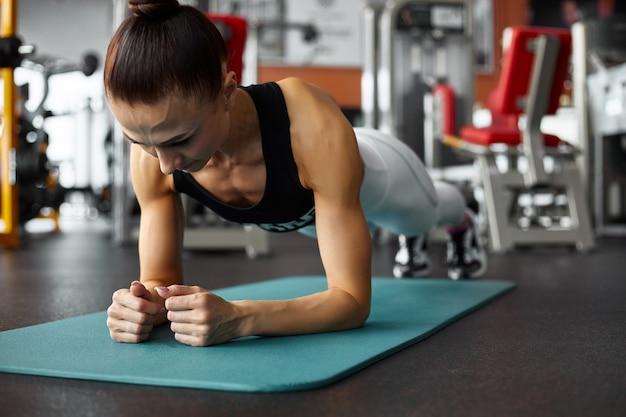 Giovane donna sportiva che fa esercizio della plancia. allenamento in palestra.