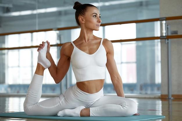 Giovane donna sportiva che fa allungamento. allenamento in palestra.