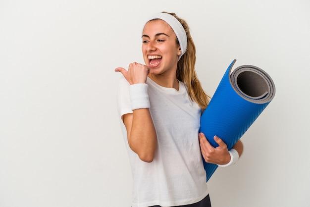 La giovane donna sportiva che tiene una stuoia isolata sui punti bianchi del fondo con il dito del pollice via, ridendo e spensierata.