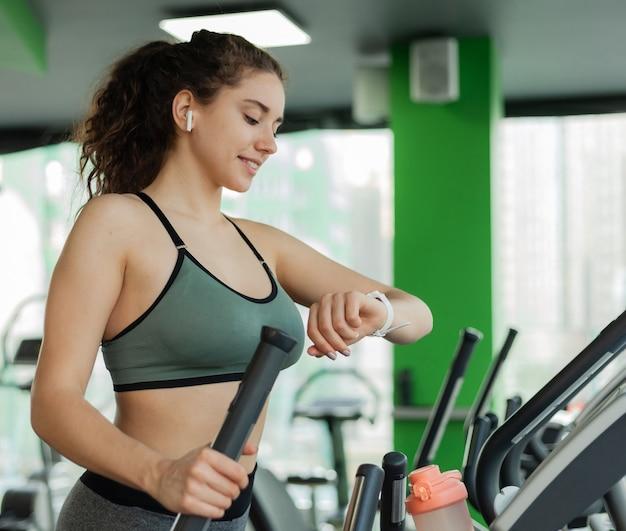 La giovane donna sportiva sta esercitando su una macchina ellittica e sta guardando il suo orologio in palestra. fitness, concetto di stile di vita sano.
