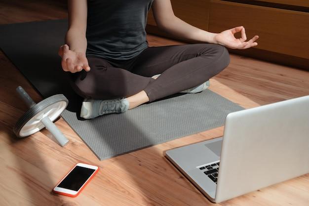 Giovane donna sportiva a praticare yoga online sul pavimento a casa utilizzando laptop e smartphone