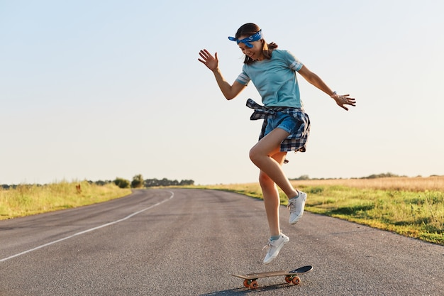 Giovane donna sportiva che guida sul longboard su strada asfaltata, facendo acrobazie su uno skateboard, donna che indossa t-shirt, pantaloncini, fascia per capelli, divertirsi da sola all'aperto.