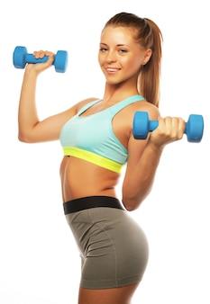 Giovane donna sportiva nella pratica dell'attrezzatura sportiva con i pesi della mano