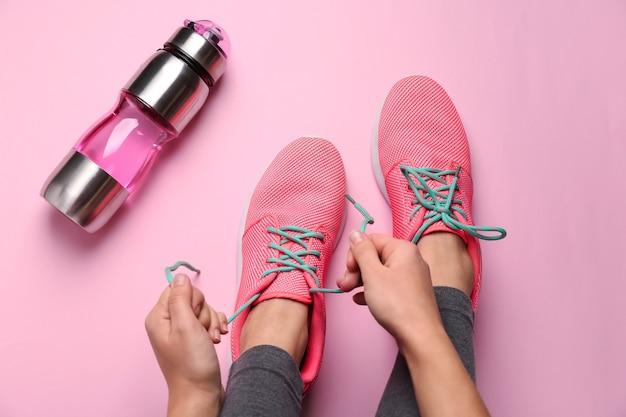 Giovane donna sportiva che lega i lacci delle scarpe prima dell'allenamento in palestra