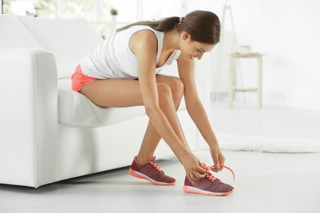 Giovane donna sportiva che lega i lacci delle scarpe a casa