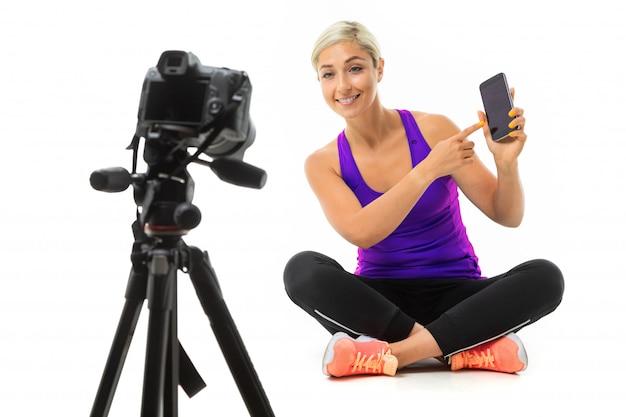 La giovane donna sportiva con i capelli chiari in un argomento sportivo nero, leggings neri e scarpe da ginnastica luminose si siede davanti alla telecamera e mostra il telefono.
