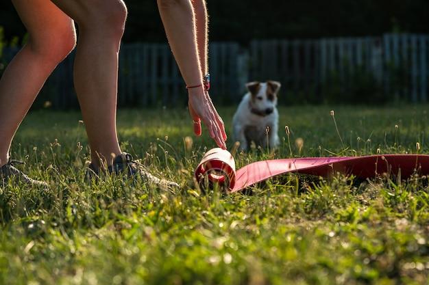 Giovane donna sportiva con capelli corti neri srotola il tappetino da yoga per esercizi di rilassamento in un parco su un prato verde, allenandosi all'aperto