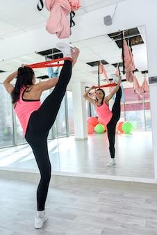L'allenamento della giovane donna sportiva esercita il bendaggio elastico in palestra. ragazza che fa esercizio di allenamento per lo stile di vita thealhty. atleta femminile