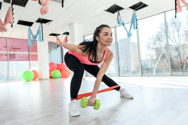 Giovane donna sportiva allenamento esercizi benda elastica in palestra. ragazza che fa esercizio di allenamento per lo stile di vita thealhty. atleta femminile