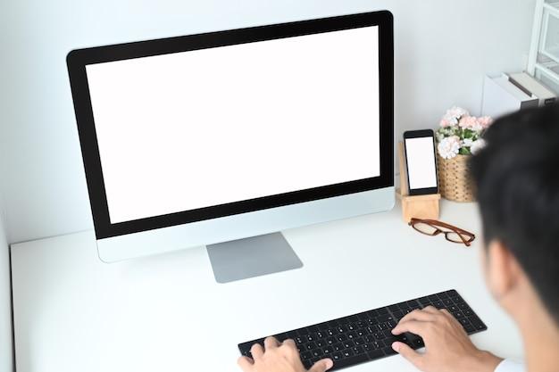 Giovane uomo di avvio che pianifica il suo lavoro con il computer sullo spazio di lavoro moderno.