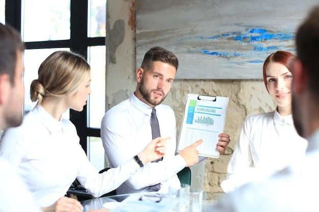 Riunione di brainstorming di lavoro di squadra di giovani imprenditori di startup per discutere l'investimento.