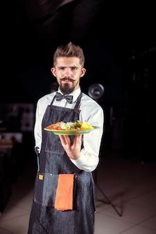 Il giovane amministratore tiene utilmente la piastra con il piatto preparato in un evento festivo.
