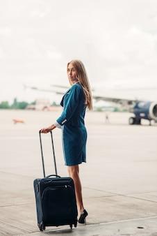 Giovane hostess con la valigia sul parcheggio degli aerei