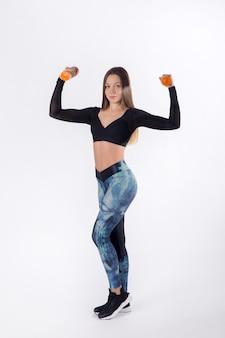 Giovane donna di forza che si allena con i manubri