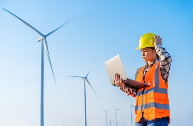 Giovane ingegnere femminile sollecitato che ha problemi a lavorare con il computer portatile contro il parco eolico
