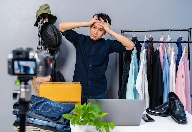 Giovane uomo stressato che vende vestiti e accessori online tramite live streaming della telecamera. commercio elettronico online da casa