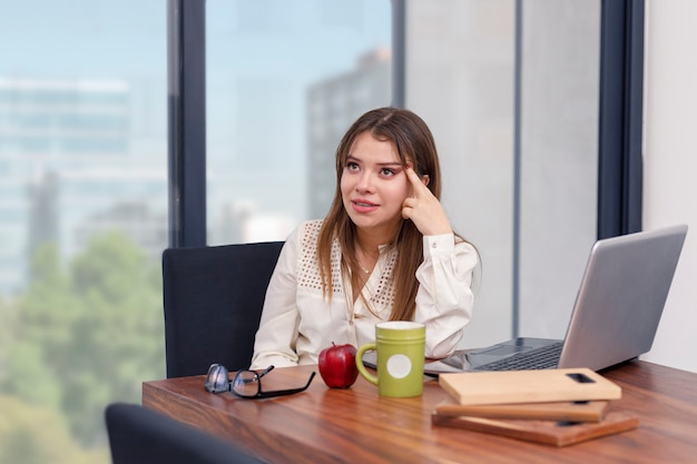 Giovane donna stressata davanti al laptop con una mela e una tazza di caffè mentre lavora