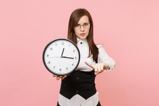 Giovane donna d'affari rigorosa in abito nero, occhiali che puntano il dito indice sulla sveglia isolata su sfondo rosa pastello. signora capo. concetto di ricchezza di carriera di successo. copia spazio per la pubblicità.