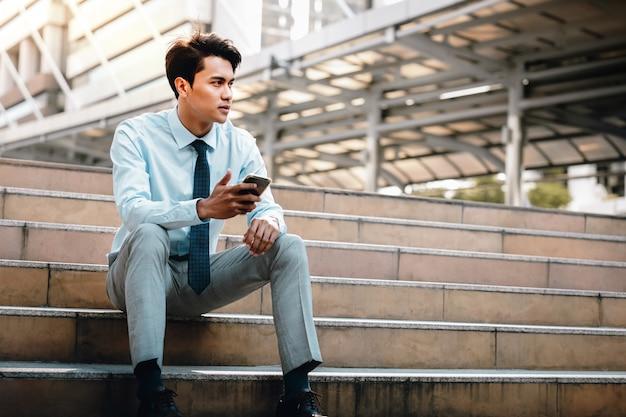 Giovane uomo d'affari asiatico sforzandosi che si siede sulla scala nella città