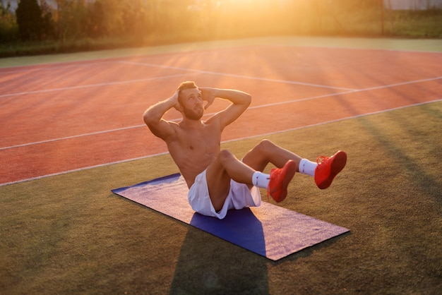 Giovane forte uomo dedicato che fa gli scricchiolii sul campo di addestramento. allenamento mattutino all'inizio dell'estate.