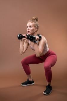 Giovane sportiva in forma forte in tuta che si siede su squat e sollevamento manubri mentre si fa uno sforzo durante l'esercizio difficile
