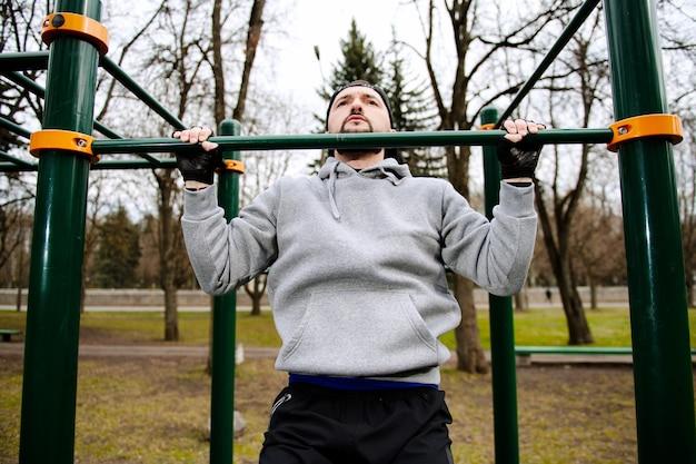 Giovane uomo forte fa pull-up su una barra orizzontale su un campo sportivo in estate in città