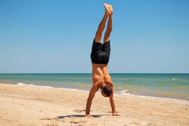 Giovane uomo forte in ottima forma fisica in verticale sulla spiaggia vicino al mare