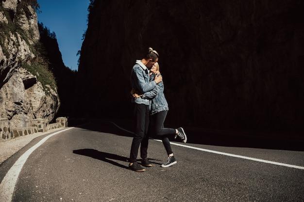 Un giovane uomo forte abbraccia la sua amata donna sullo sfondo delle montagne di pietra