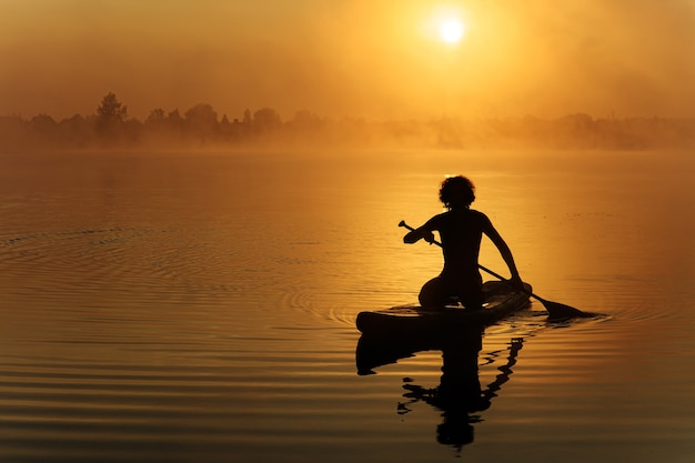 Giovane uomo forte in silhouette utilizzando la pagaia per galleggiare sulla tavola di sup al lago nebbioso.