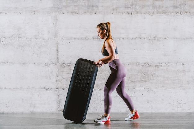 Giovane forte sportiva caucasica muscolare in abiti sportivi con coda di cavallo lanciando pneumatico. concetto di stile di vita sano.