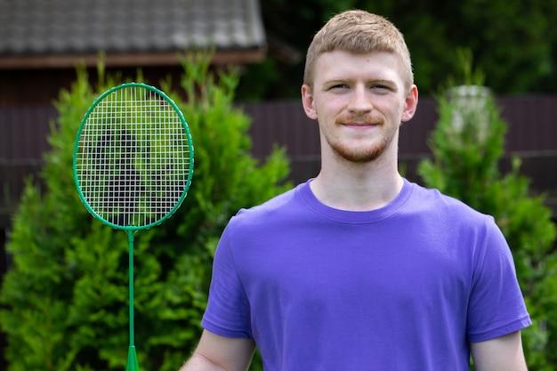 Uomo caucasico di giovane sport forte che posa con la racchetta di badminton sulla natura verde. concetto di gioco amatoriale di badminton, attività estive all'aperto.