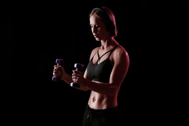Giovane donna forte con addome perfetto e braccia forti si esercita con manubri su sfondo nero black
