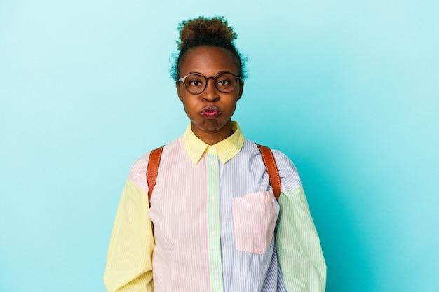 Giovane studente americano africano donna su sfondo isolato soffia le guance, ha un'espressione stanca. concetto di espressione facciale.