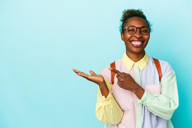 Giovane studente americano africano donna su sfondo isolato eccitato tenendo una copia spazio sul palmo.