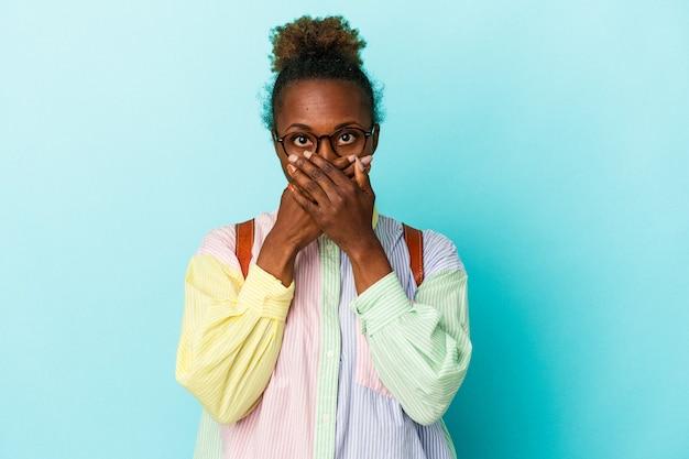 Giovane studente americano africano donna su sfondo isolato scioccato che copre la bocca con le mani.