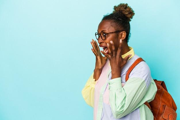 Giovane studentessa afroamericana su sfondo isolato grida forte, tiene gli occhi aperti e le mani tese.