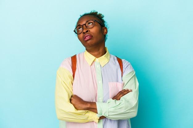 Giovane studente americano africano donna su sfondo isolato stanco di un compito ripetitivo.