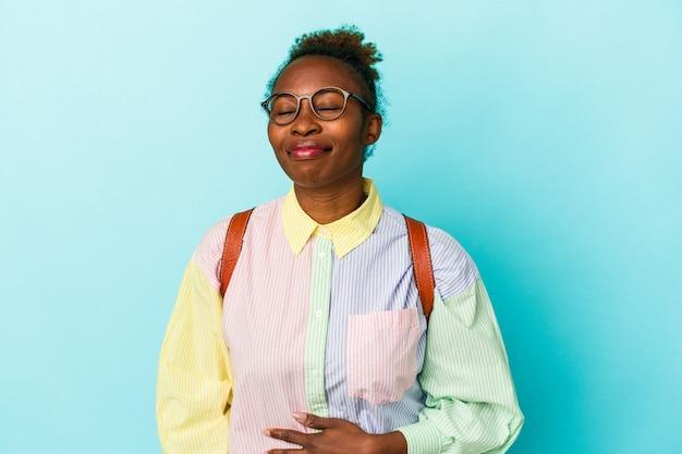 Giovane studente americano africano donna su sfondo isolato tocca la pancia, sorride dolcemente, mangiare e concetto di soddisfazione.