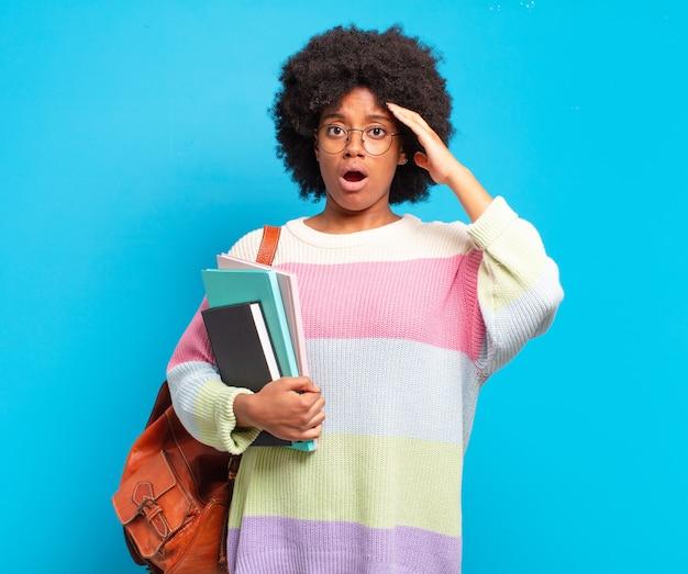 Giovane studentessa afro che sembra felice, stupita e sorpresa, sorridente e realizzando incredibili e incredibili buone notizie