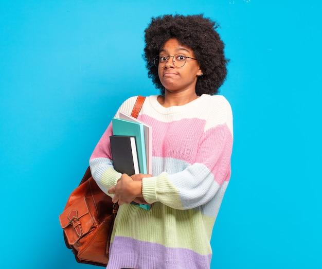 Giovane studentessa afro che scrolla le spalle, sentendosi confusa e incerta, dubitando con le braccia incrociate e lo sguardo perplesso