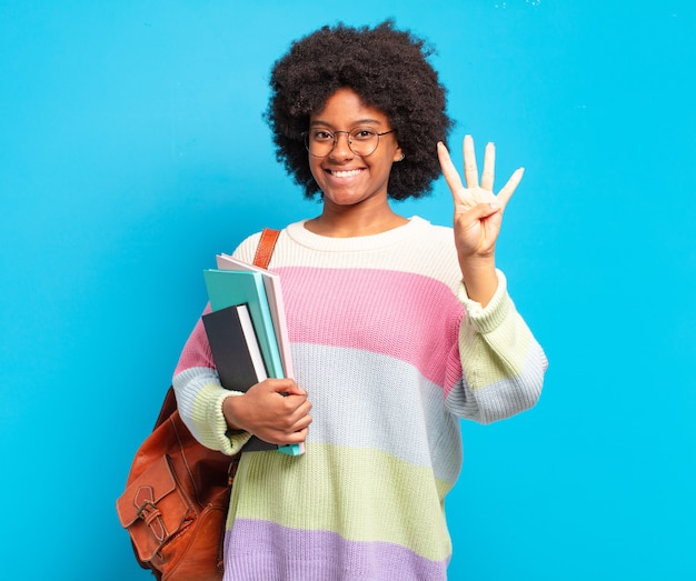 Giovane studente afro donna sorridente e guardando amichevole, mostrando il numero quattro o il quarto con la mano in avanti, il conto alla rovescia
