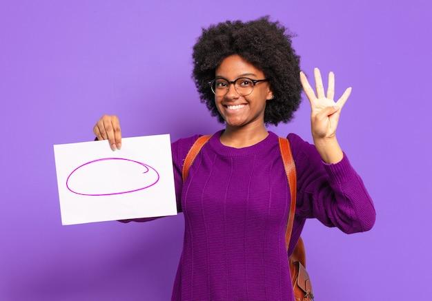 Giovane studentessa afro che sorride e sembra amichevole, mostrando il numero quattro o il quarto con la mano in avanti, conto alla rovescia