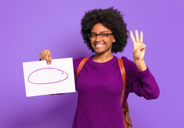 Giovane studente afro donna sorridente e guardando amichevole, mostrando il numero tre o terzo con la mano in avanti, il conto alla rovescia