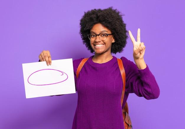 Giovane studente afro donna sorridente e guardando amichevole, mostrando il numero due o il secondo con la mano in avanti, il conto alla rovescia