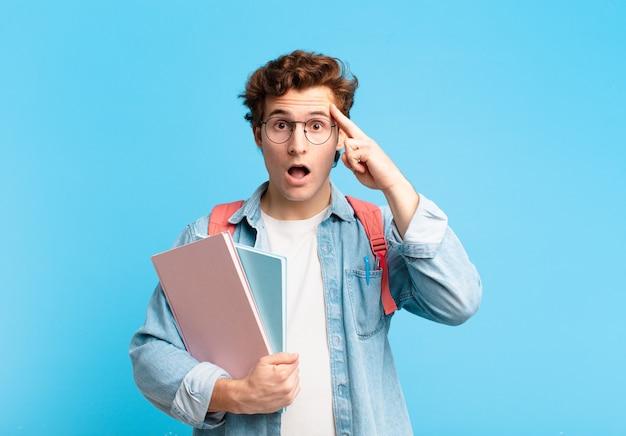 Giovane studente che sembra sorpreso, a bocca aperta, scioccato, realizzando un nuovo pensiero, idea o concetto