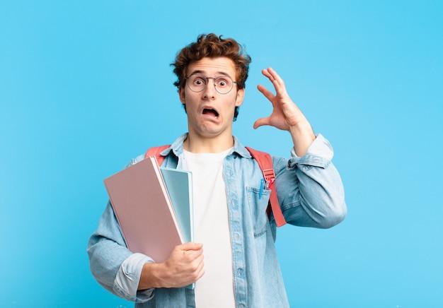 Giovane studente che urla con le mani in aria, sentendosi furioso, frustrato, stressato e turbato