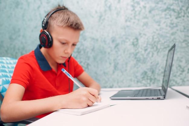 Il giovane ragazzo dello studente con la penna di scrittura del computer portatile impara e prepara il ritorno a scuola.